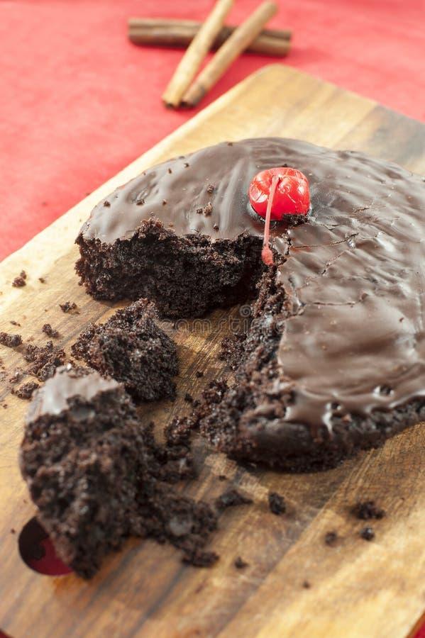 Bolo de chocolate redondo caseiro mordido com canela e cereja. fotografia de stock royalty free