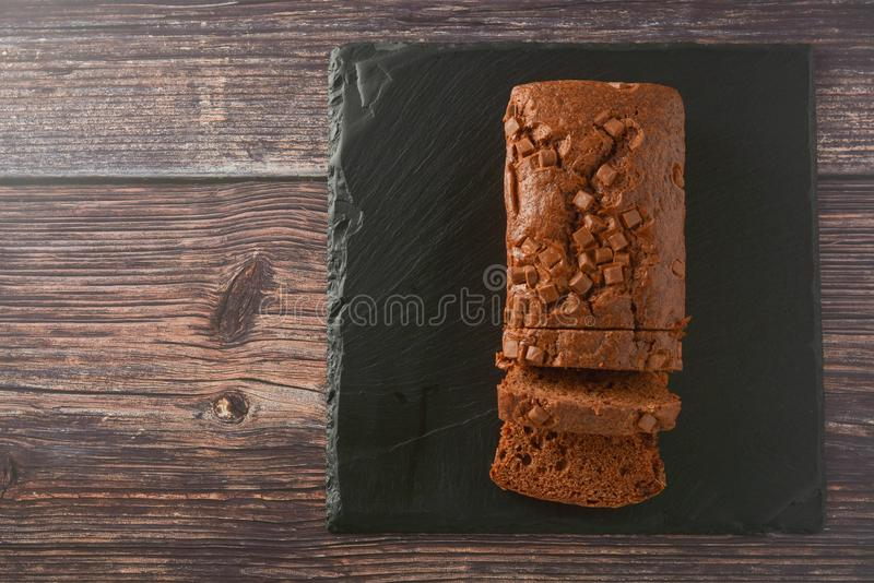 Bolo de chocolate Vista superior do bolo com pedaços de chocolate, fundo de madeira da libra foto de stock