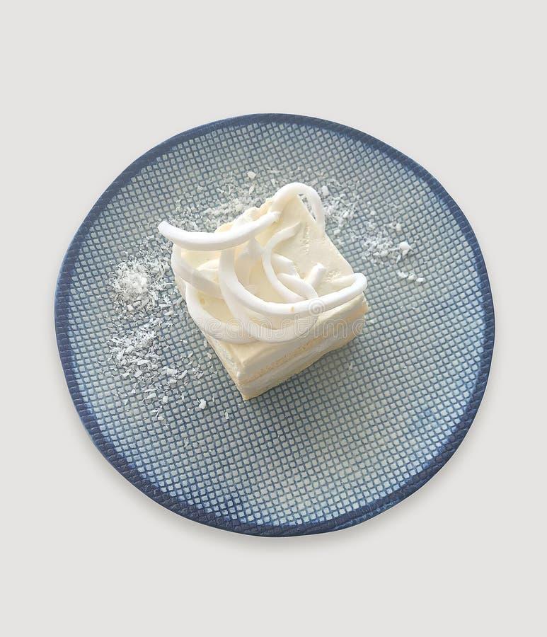 Bolo de coco no prato com a peça do grampeamento no fundo branco fotos de stock royalty free