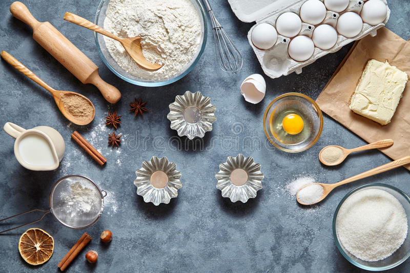 Bolo de cozimento na cozinha - ovos dos ingredientes da receita da massa, farinha, leite, manteiga, açúcar e pino do rolo na tabe fotografia de stock
