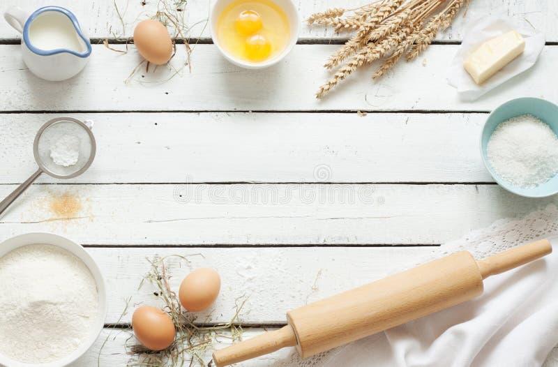 Bolo de cozimento na cozinha rústica - ingredientes da receita da massa na tabela de madeira branca imagens de stock royalty free