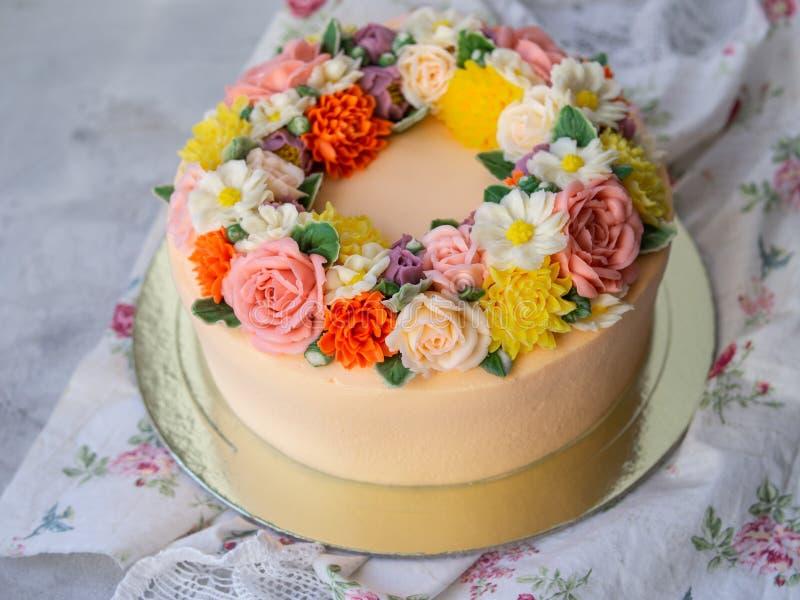 Bolo de creme amarelo decorado com flores do buttercream - peônias, rosas, crisântemos, cravos - no fundo de madeira branco imagem de stock royalty free