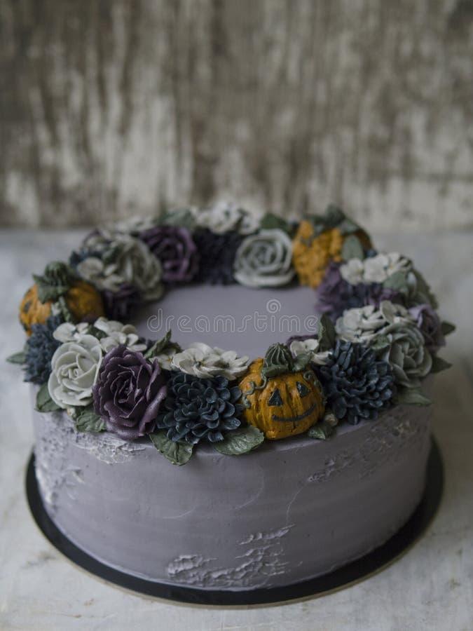 Bolo de creme cinzento decorado com as flores e as abóboras escuras do buttercream no fundo rústico Bolo de Dia das Bruxas Bolo u fotografia de stock