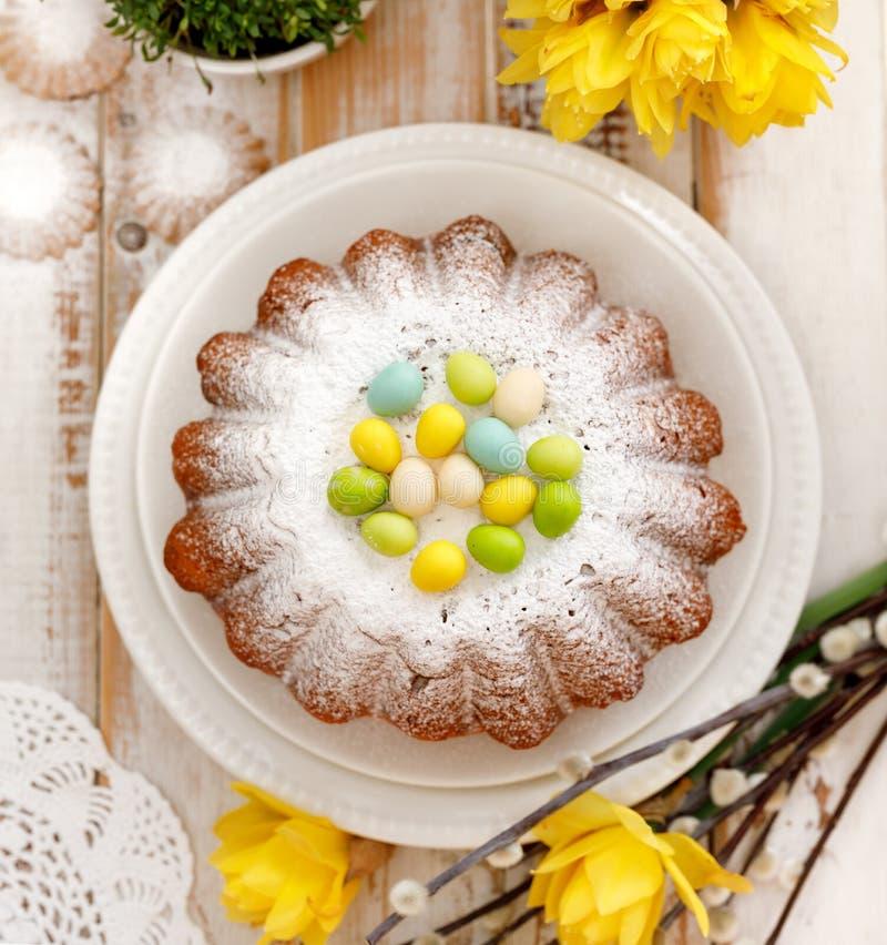 Bolo de fermento da Páscoa polvilhado com o açúcar pulverizado, decorado com ovos do maçapão imagem de stock