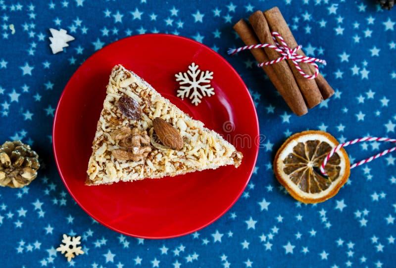 Bolo de frutas, decoração, placa com um bolo e uma xícara de café vermelha ou chá no placemat azul Ano novo fotos de stock royalty free