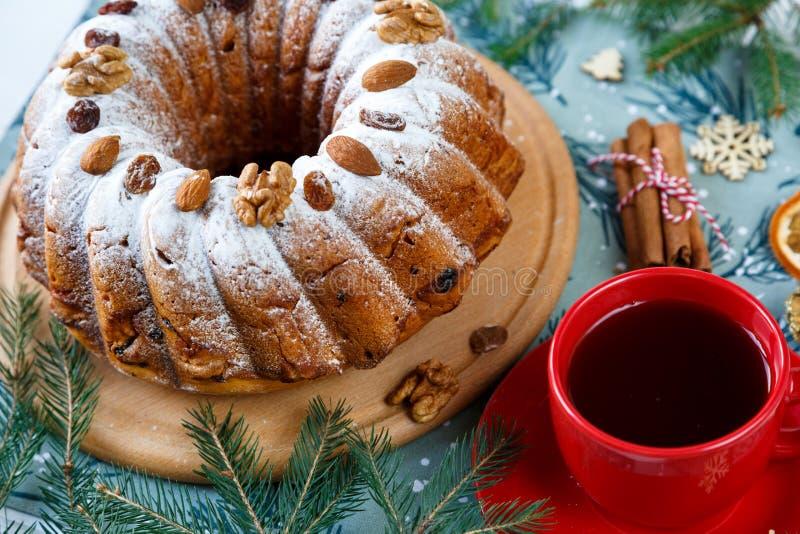 Bolo de frutas, decoração, ramos do abeto vermelho, placa com um bolo e uma xícara de café vermelha ou chá no placemat azul Ano n imagem de stock