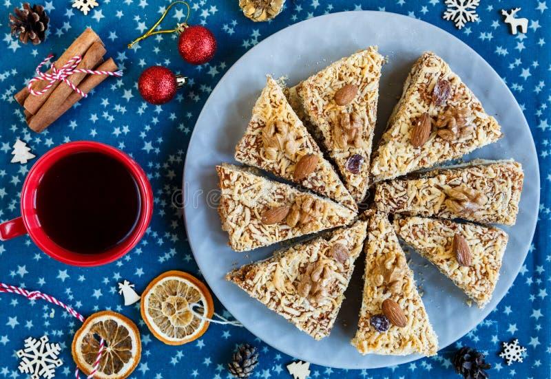 Bolo de frutas, decoração, ramos do abeto vermelho, placa com um bolo e uma xícara de café vermelha ou chá no placemat azul Ano n fotografia de stock royalty free