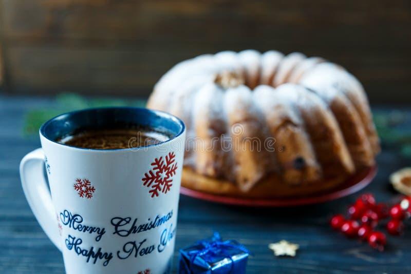 Bolo de frutas tradicional para o Natal decorado com açúcar e porcas pulverizadas, passas e xícara de café Pastelaria caseiro de  foto de stock