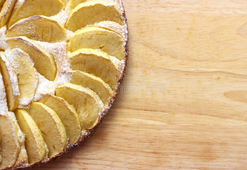 Bolo de maçã caseiro espanado com mentiras do açúcar de crosta de gelo em um espaço livre de opinião superior de placa de madeira imagens de stock