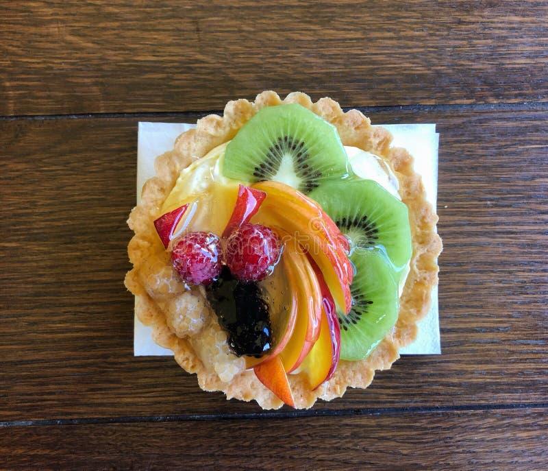 Bolo de pastelaria delicioso com frutas frescas em mesa imagem de stock