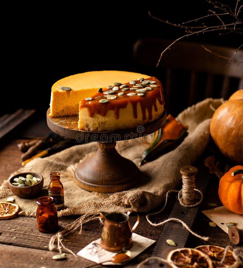 Bolo de queijo alaranjado da abóbora saboroso caseiro no suporte de madeira do bolo na tabela marrom rústica imagem de stock royalty free