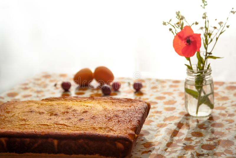 Bolo de queijo caseiro em uma placa de corte de madeira, flores na garrafa e certos frutos na tabela imagens de stock royalty free