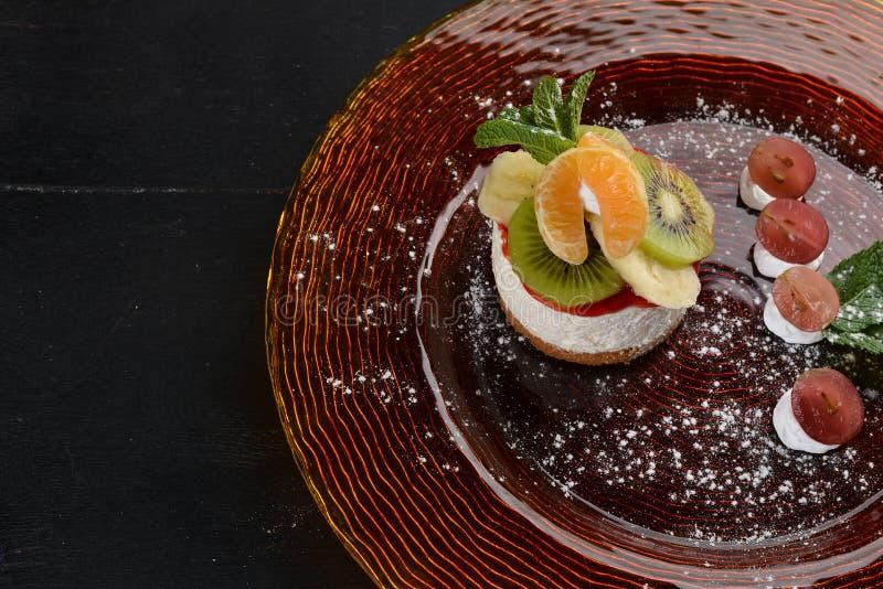 Bolo de queijo com frutos e creme Sobremesa Em uma superfície de madeira fotos de stock royalty free