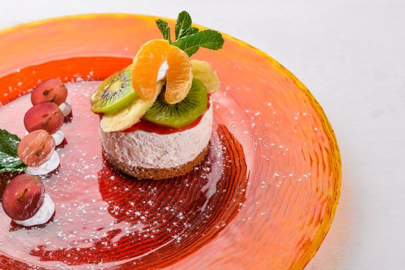 Bolo de queijo com frutos e creme Sobremesa Em uma superfície de madeira imagem de stock royalty free