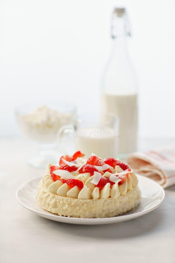 Bolo de queijo delicado da morango com coco Bolo caseiro delicioso com as bagas frescas na tabela clara fotografia de stock