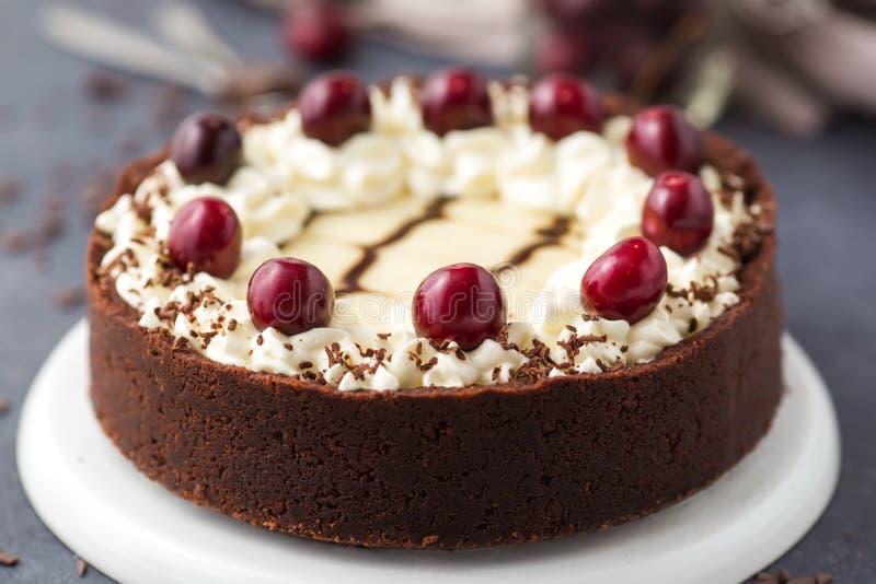 Bolo de queijo do chocolate com cerejas em um fundo escuro imagem de stock