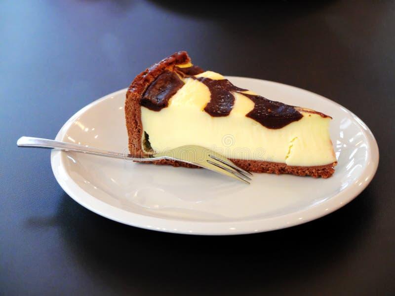 Bolo de queijo na placa branca com forquilha fotografia de stock