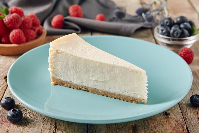 Bolo de queijo de New York no fim azul da placa acima fotos de stock royalty free