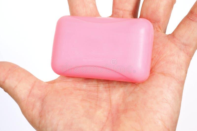 Bolo de sabão rosa deita-se sobre uma palma masculina Fundo branco, não isolado Higiene, proteção do coronavírus, segurança e pre fotografia de stock royalty free