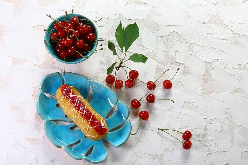 Bolo delicioso do creme com cerejas em uma placa de cristal em um fundo claro Imagem com espaço da cópia Vista superior imagens de stock