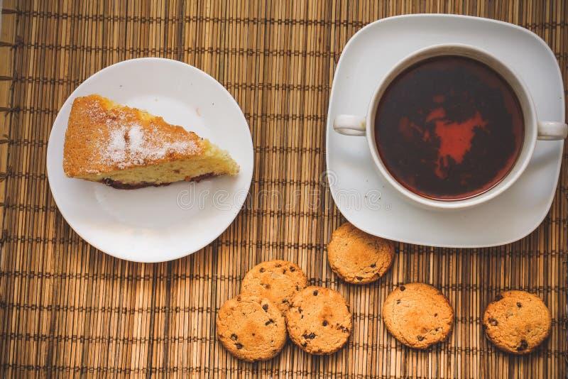 Bolo do biscoito da ameixa para um copo do chá quente em um fundamento da palha com c fotos de stock royalty free