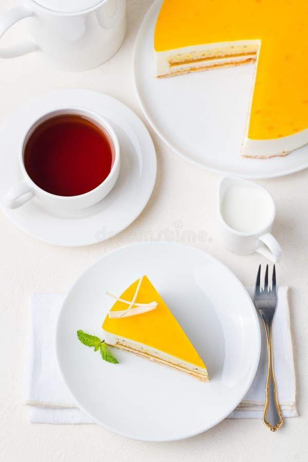 Bolo do fruto de paixão, sobremesa da musse em uma placa branca com o copo do chá Vista superior fotografia de stock royalty free