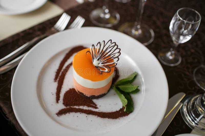 Bolo do fruto de paixão, sobremesa da musse em uma placa branca com o copo do chá Vista superior imagem de stock royalty free