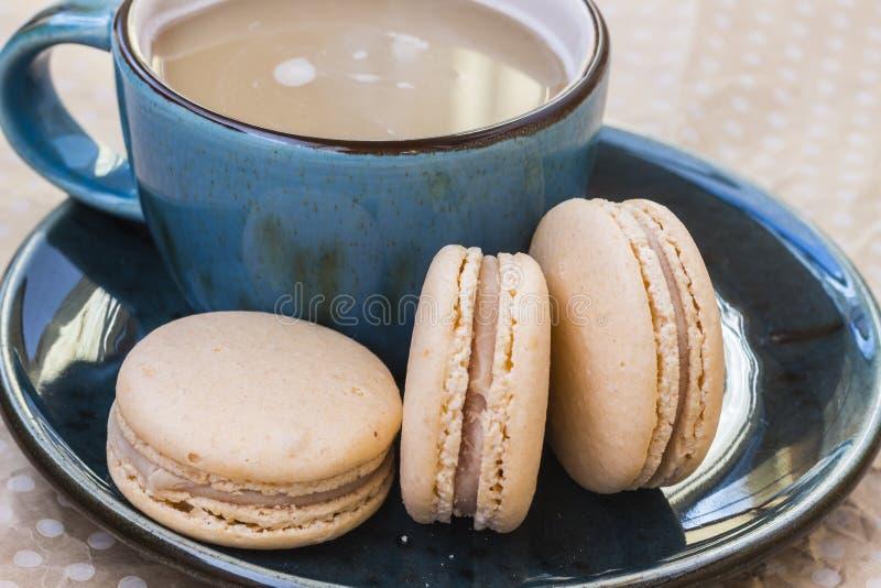 Bolo do macarrão três e uma xícara de café em um fundo bege do às bolinhas Vista superior fotografia de stock