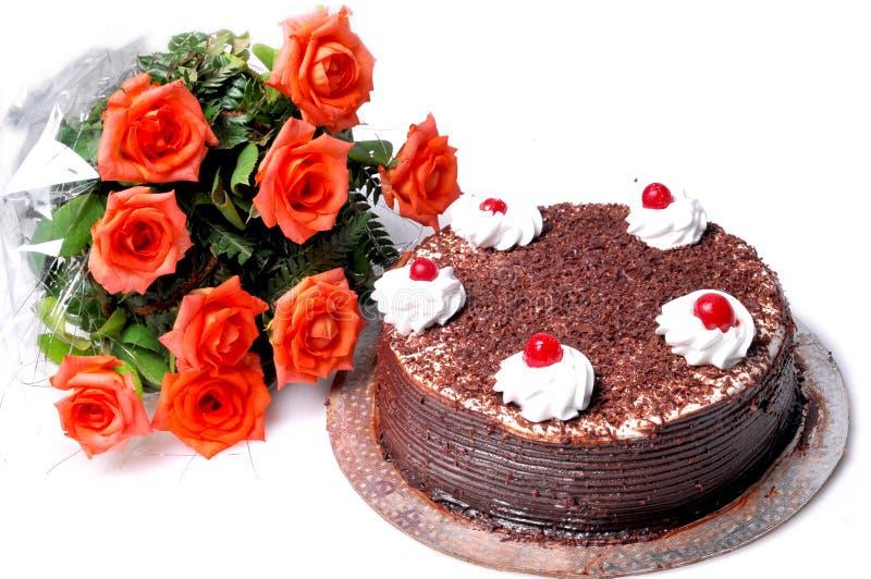Bolo e flores de aniversário imagem de stock