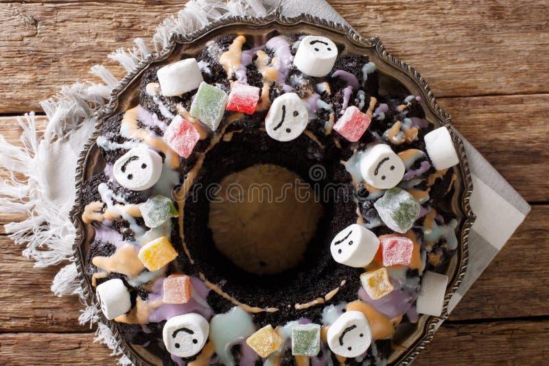 Bolo escuro engraçado de Bundt com frutos cristalizados, marshmallow e cor imagem de stock