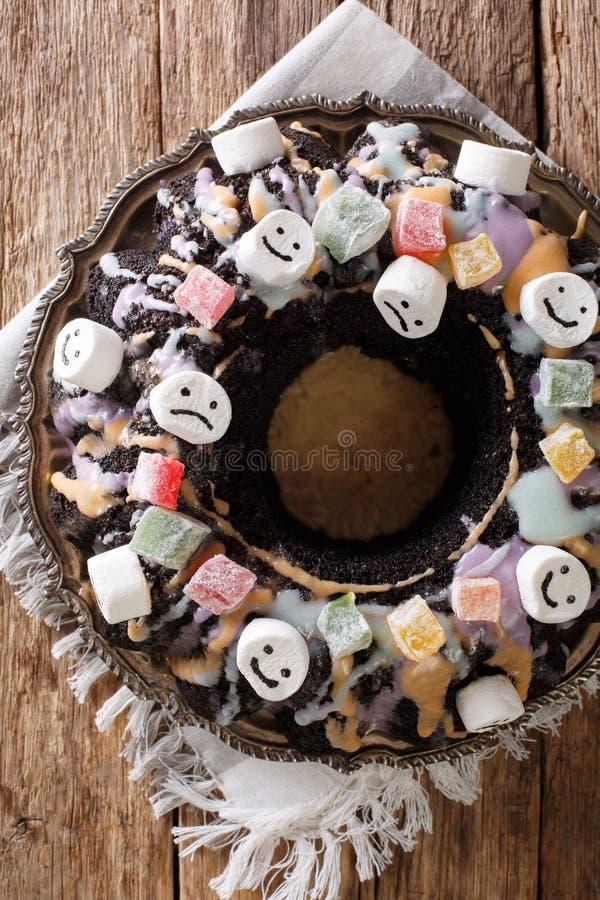 Bolo escuro engraçado de Bundt com frutos cristalizados, marshmallow e cor fotografia de stock
