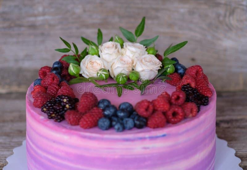 Bolo home bonito com o creme cor-de-rosa e roxo, decorado com rosas brancas e bagas de Blackberry, mirtilos, framboesas imagens de stock