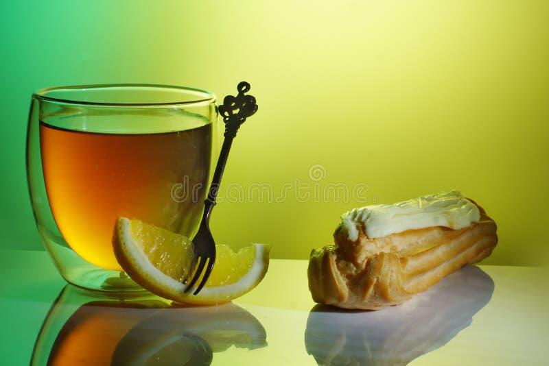Bolo, limão e chá em um vidro transparente na tabela com uma reflexão em um fundo verde-amarelo foto de stock royalty free