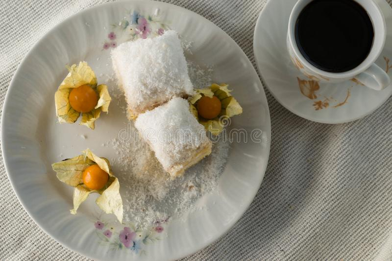 Bolo Raffaello com fatias em um prato sobre uma mesa com café fotografia de stock royalty free