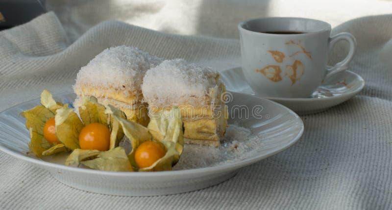 Bolo Raffaello com fatias em um prato em uma mesa com café fotos de stock royalty free