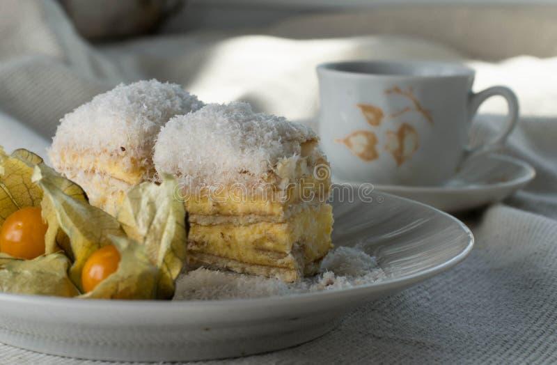 Bolo Raffaello com fatias em um prato em uma mesa com café imagens de stock royalty free