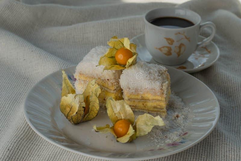 Bolo Raffaello com fatias em um prato em uma mesa com café imagens de stock