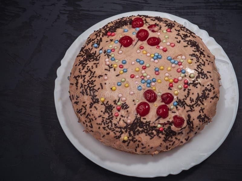 Bolo redondo caseiro com molho colorido do caramelo em um tiro branco do close-up da placa foto de stock