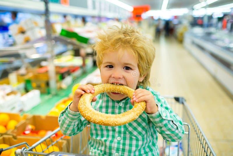 Bolo saboroso O menino morde o bagel com sésamo no supermercado Produtos da padaria Compra da compra para o alimento Alimento da  foto de stock royalty free