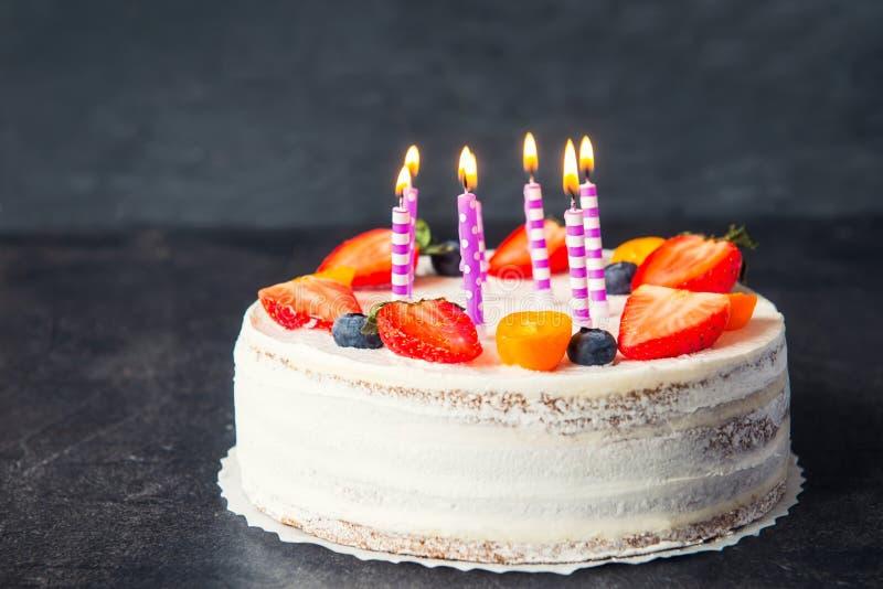 Bolo saudável do yougurt do aniversário branco com morangos, os mirtilos e velas frescos na obscuridade - cinzenta, fundo de pedr foto de stock