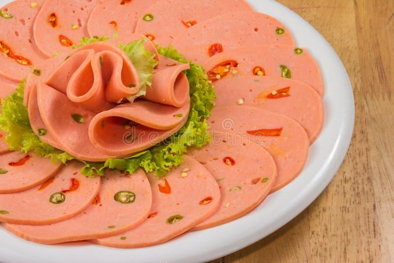 Bologna épicé dans un plat blanc sur le dessus de table images stock