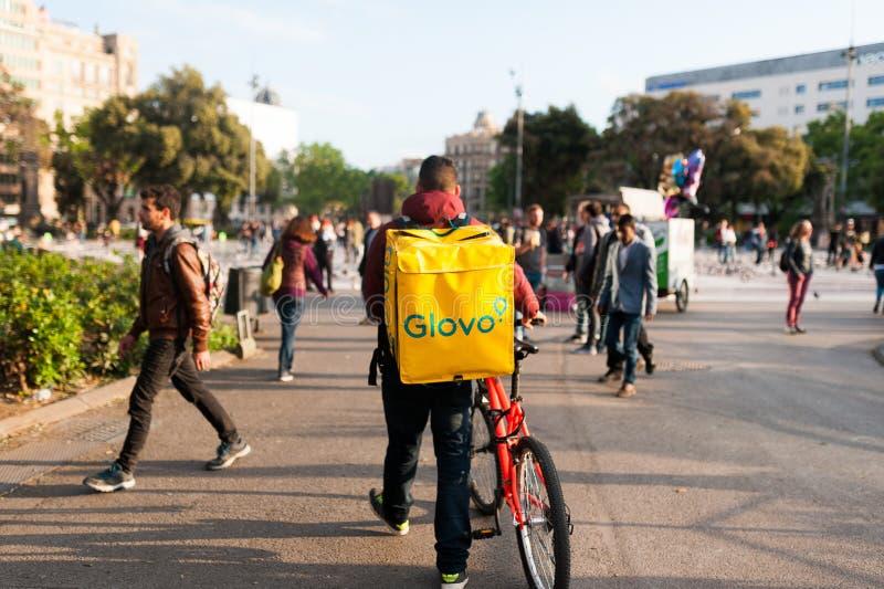 Bologna, Italia - 13 aprile 2019: giovane cavaliere di glovo del ragazzo che effettua consegna sul suo funzionamento della bici n immagine stock libera da diritti
