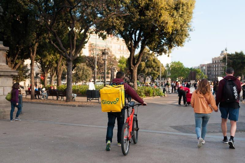 Bologna, Italia - 13 aprile 2019: giovane cavaliere di glovo del ragazzo che effettua consegna sul suo funzionamento della bici n fotografia stock