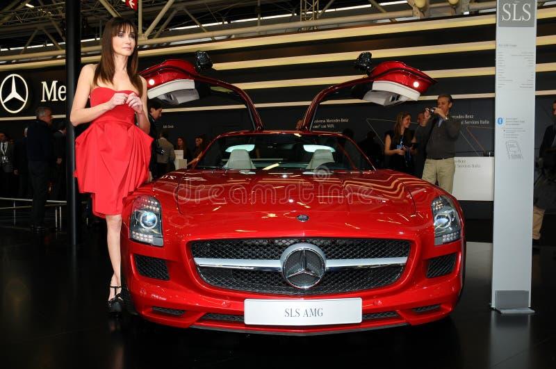 BOLOGNA, ITALIEN - 2. DEZEMBER 2010: schönes Mode-Modell wirft bei Mercedes Stand mit Mercedes SLS AMG an der Bologna-Autoausstel stockbild