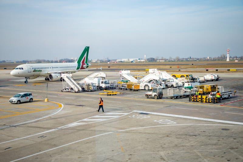 Bologna Italien - 10 02 2019: Upptagen flygplatssikt med flygplan- och servicemedel-, lopp- och branschbegrepp royaltyfri foto