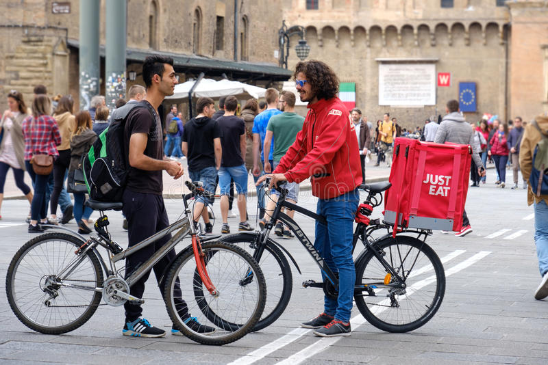 Bologna, Italy, 1 May 2017 - A Just Eat bike deliver courier spe. Ak with another cyclist in the Bologna`s main square royalty free stock images