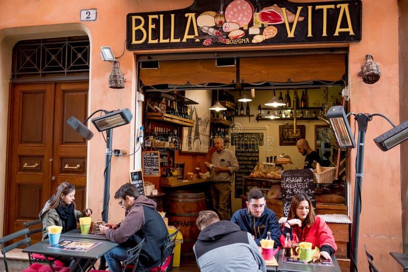 Bologna, Włochy - 20 mogą 2019: miejscowi i turysta jedzą outside tradycyjnego włocha baru łasowanie i pić cieszyć się tradycyjny zdjęcia stock