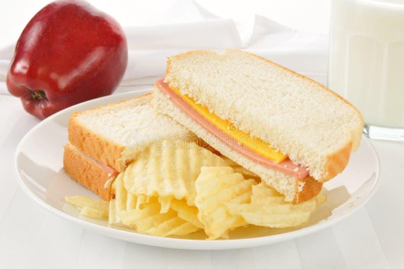 Bolognasmörgåsen med ett äpple och mjölkar fotografering för bildbyråer