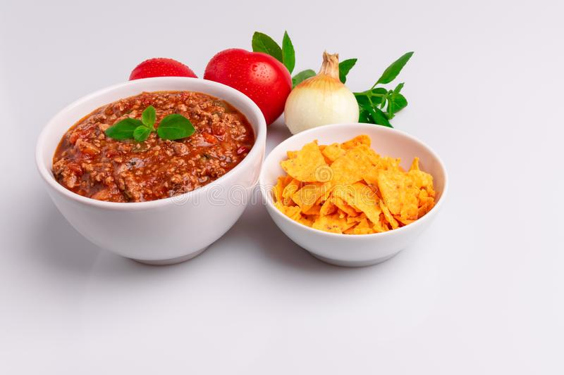 Bolognese also know as Bolognesa or Bolonhesa sauce and corn chips nachos in a white bowl isolated in white background, soft stock image