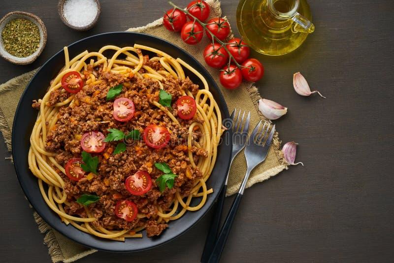 Bolognese bucatini för pasta med slarvsylta och tomater, mörk träbakgrund, bästa sikt, kopieringsutrymme royaltyfri fotografi